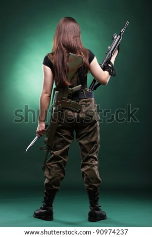 Beautiful woman with rifle plastic Military Army girl Holding Gun green background - stock photo