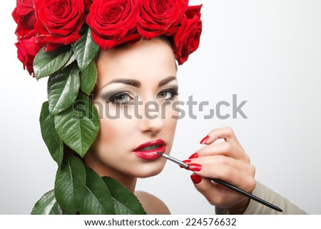 Beautiful woman with roses and leafs in her hair. She gets lipstick in preparation for her photo shooting.