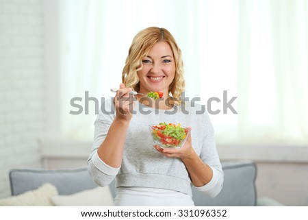 Beautiful woman with salad on home interior background