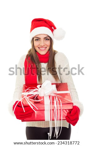 Beautiful woman with Santa Claus hat smiling holding big Christmas gift box. Closeup of cute young Caucasian brunette woman holding a present wearing cozy winter clothes isolated on white background. - stock photo