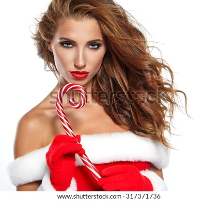 Beautiful woman with santa costume  holding red-white Christmas Lollipop