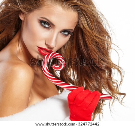 Beautiful woman with santa hat holding red-white Christmas Lollipop - stock photo
