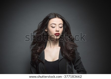 Beautiful woman with sexy dark red lips and fashion eye make-up. Close-up portrait of female model posing in studio. - stock photo