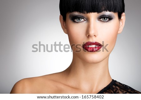 Beautiful woman with  sexy red lips and fashion color eye makeup. Closeup portrait of a female model. - stock photo