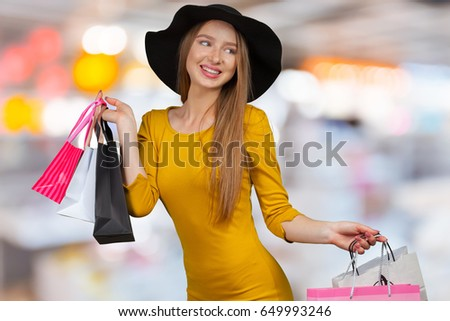 Beautiful woman with shopping bags in big mall
