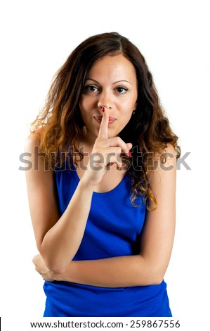Beautiful woman with silence sign isolated on white background. Closeup portrait of serious modern girl with long hair holding finger near pink lips - stock photo