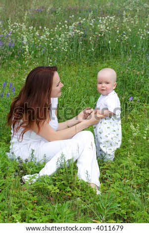 Beautiful woman with small kid at green meadow - stock photo