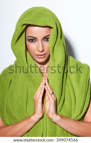 Beautiful woman with smokey makeup in arabic style fashion look with traditional welcoming gesture - stock photo