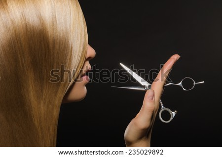 Beautiful woman with straight hair and scissors on black background - stock photo