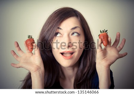 beautiful woman with strawberries on gray background