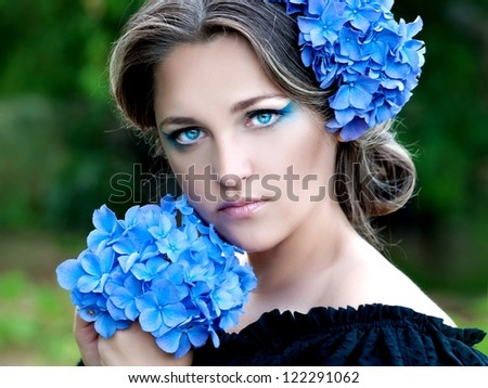beautiful woman with stylish makeup and blue flower of  hydrangeas in your hair - stock photo