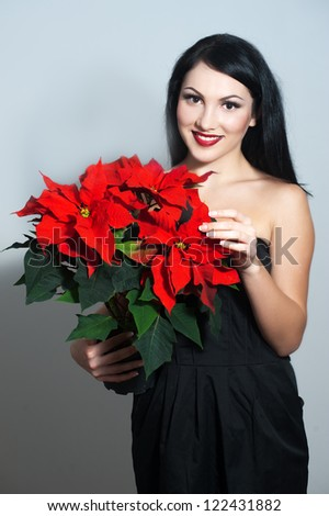 Beautiful woman with stylish makeup and red xmas flowers in her hands. Xmas style