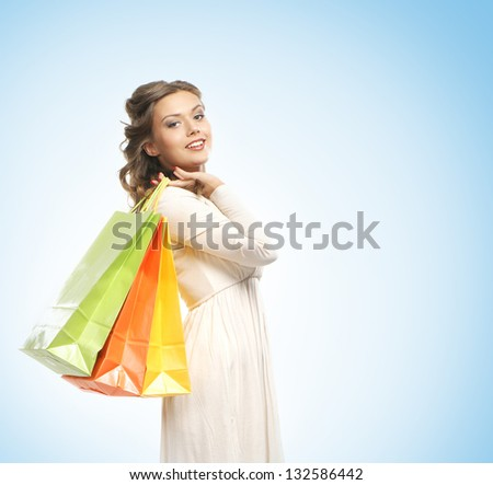 Beautiful woman with the bright shopping bags over the blue background - stock photo