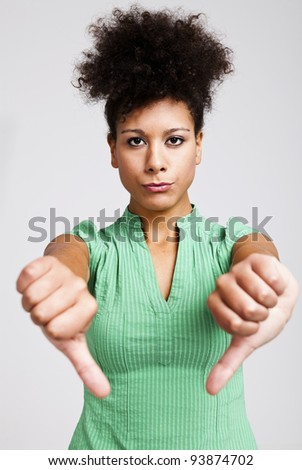 Beautiful woman with thumbs down. Studio shot.