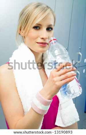 Beautiful woman with towel and bottle of water after sport training - stock photo