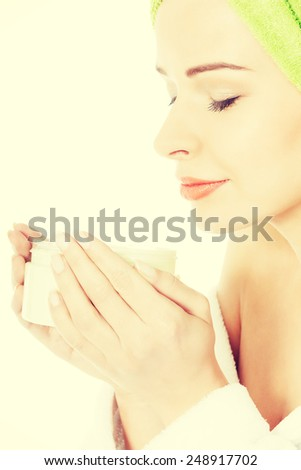 Beautiful woman with towel and in bathrobe with body lotion. Spa concept.  - stock photo