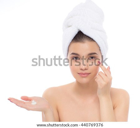 Beautiful woman with towel on head. The face cream. - stock photo