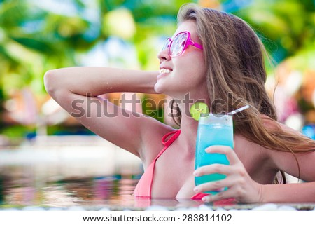 Beautiful woman with tropical cocktail in the pool - stock photo