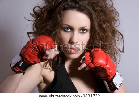 Beautiful woman with wild hair and boxing gloves - stock photo