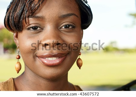 beautiful woman with wooden earrings looks at you outdoors with a smile - stock photo