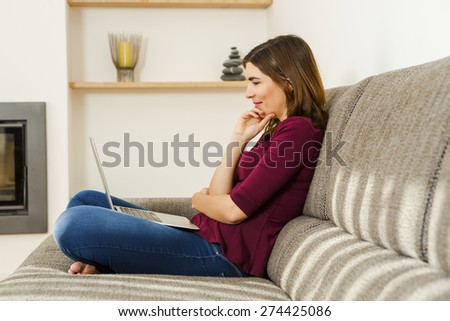 Beautiful woman working from the confort of home with her laptop - stock photo
