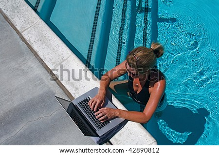 Beautiful woman working on her communications poolside on holiday