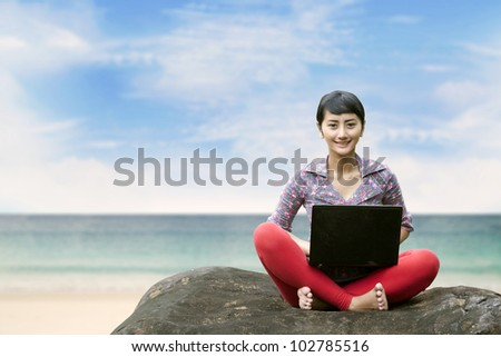 Beautiful woman working on laptop at the beach. Copy space is available for your text - stock photo