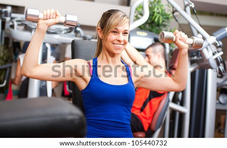 Beautiful woman working out in a fitness club - stock photo