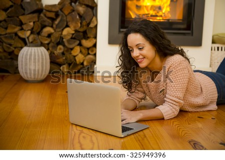 Beautiful woman working with a laptop at the warmth of the fireplace - stock photo