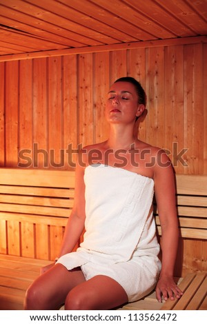 Beautiful woman wrapped in white hotel relaxing a sauna - stock photo