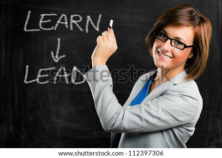 Beautiful woman writing a motivational concept on a blackboard - stock photo