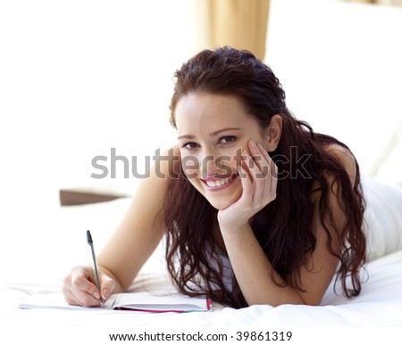 Beautiful woman writing notes lying in bed