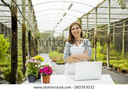 Beautiful woman wroking in a greenhouse and looking at camera while smiling - stock photo