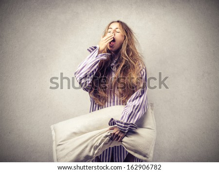 beautiful woman yawning with a pillow in hand - stock photo