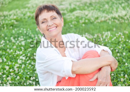beautiful woman 50 years relax on the grass and smiling in summer - stock photo