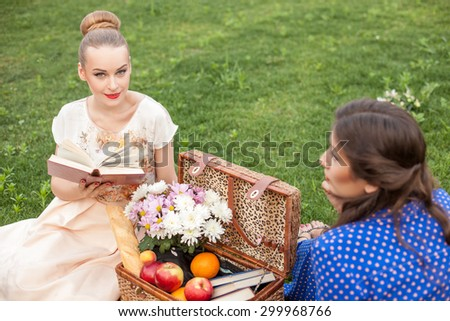 Beautiful women are resting and sitting on grass near the basket of food. The blond girl is reading a poem aloud and smiling with pleasure. Her friend is listening to her attentively - stock photo