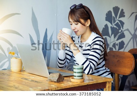 Beautiful women are using laptops. At coffee shop in To connect with customers via social networks.  - stock photo