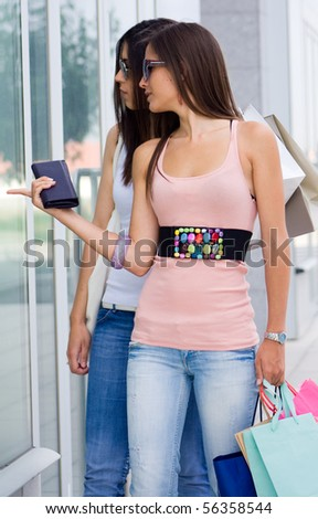 Beautiful women at a shopping center with bags - stock photo