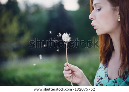 Beautiful women blowing the dandelion at the park