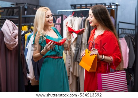 Beautiful women choosing red shoes in the clothing store. Female friends having fun shopping in the boutique