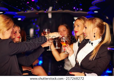 beautiful women clinking glasses in limousine - stock photo