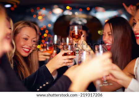 beautiful women clinking glasses in limousine. focus on glasses - stock photo