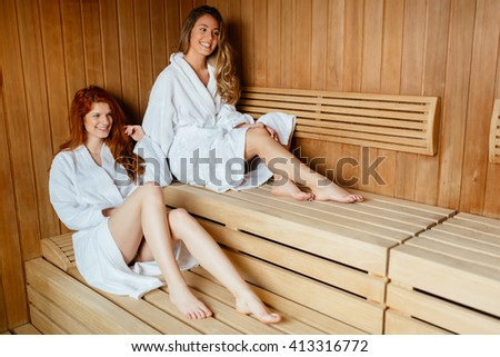 Beautiful women enjoying sauna treatment in bathrobes - stock photo
