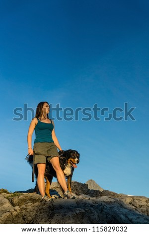 Beautiful women hiking with her Bernese Mountain dog in the mountains. - stock photo