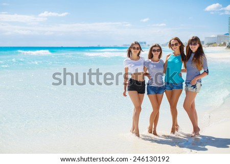 Beautiful women in bikini at the seaside. Four gorgeous young women posing at the beach near blue ocean.  - stock photo
