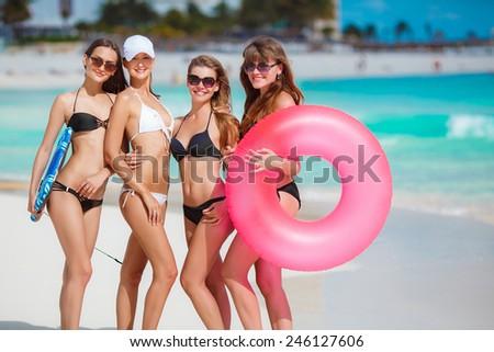 Beautiful women in bikini at the seaside. Joyful team of friends having fun at the ocean beach. Four slim young girls in bikinis on the beach enjoying the sun and blue water. - stock photo