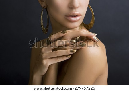 Beautiful Women Lips with Stylish Golden Shiny Lipstick and Hands with Golden Manicure and Gold Jewelery on dark background. Make up, Fashion, Beauty. Nail Care - stock photo