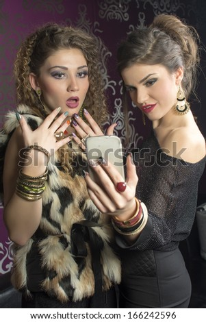 Beautiful women looking surprised at cellphone