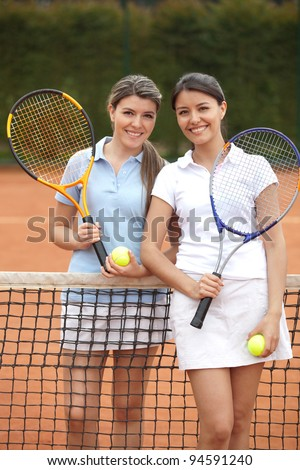Beautiful women playing tennis and looking happy - stock photo