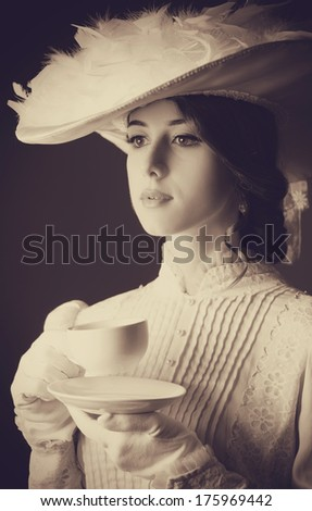 Beautiful women with cup of tea. Photo in old color image style. - stock photo
